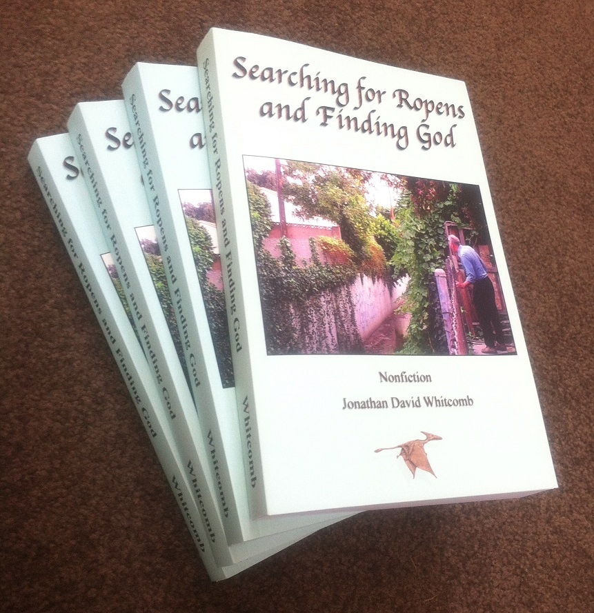 """small pile of books: """"Searching for Ropens and Finding God"""" by Jonathan Whitcomb"""