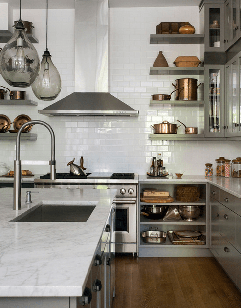 French-inspired kitchen with honed Carrara marble countertops, handblown glass pendant lights, and Mauviel copper cookware to complement the white tile and 48-inch stainless steel Wolf range. From Interior designer Tanya Capaldo's gorgeously chic renovated 19th-century brownstone.