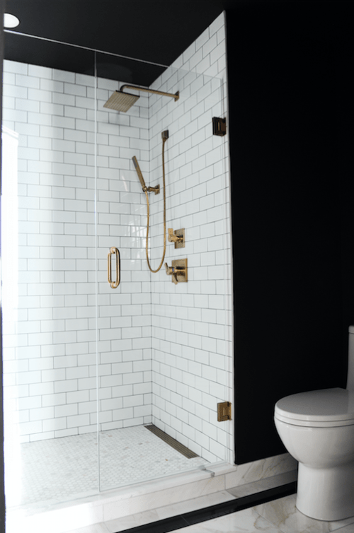 Perfectly dramatic bathroom with black walls, white subway tiles and brass fixtures.