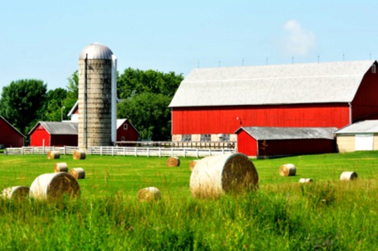 Pretty red barn with silver silo and round bales of hay in the field