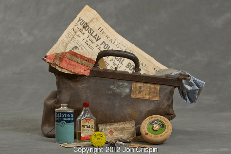 "Suticase including a newspaper from the 30s with a headline of ""Yugoslav political - undescipherable"" and various men's toiletries."