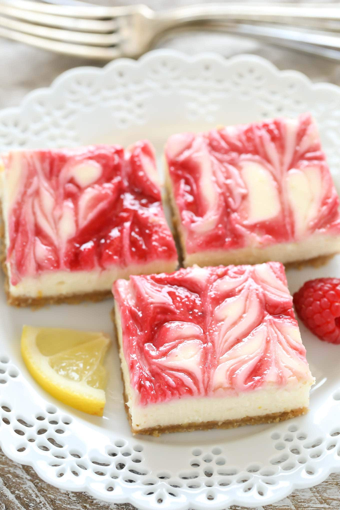 Three lemon raspberry cheesecake bars on a white dessert plate.