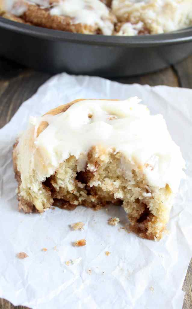 A 1 hour cinnamon roll with a bite missing on a piece of paper. A pan of cinnamon rolls rests in the background.