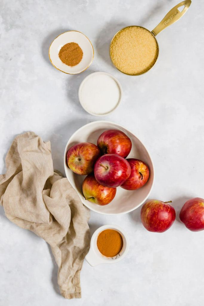 The ingredients needed to make apple butter in various bowls and measuring cups on a gray surface.
