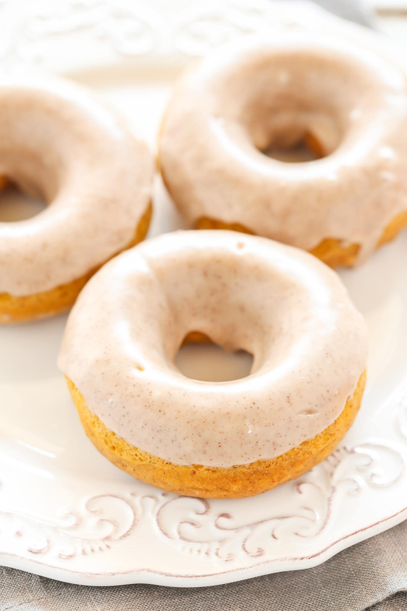 An easy recipe for baked pumpkin donuts topped with a maple cinnamon glaze. Perfect for an easy and delicious fall breakfast!