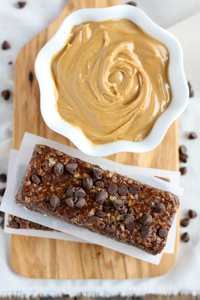 Overhead view of a stack of healthy peanut butter chocolate chip granola bars and a bowl of peanut butter on a wood board.