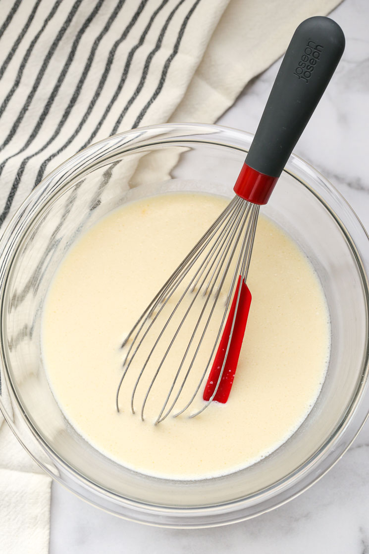 A clear bowl filled with the wet ingredients for pancake batter and a red and black whisk.