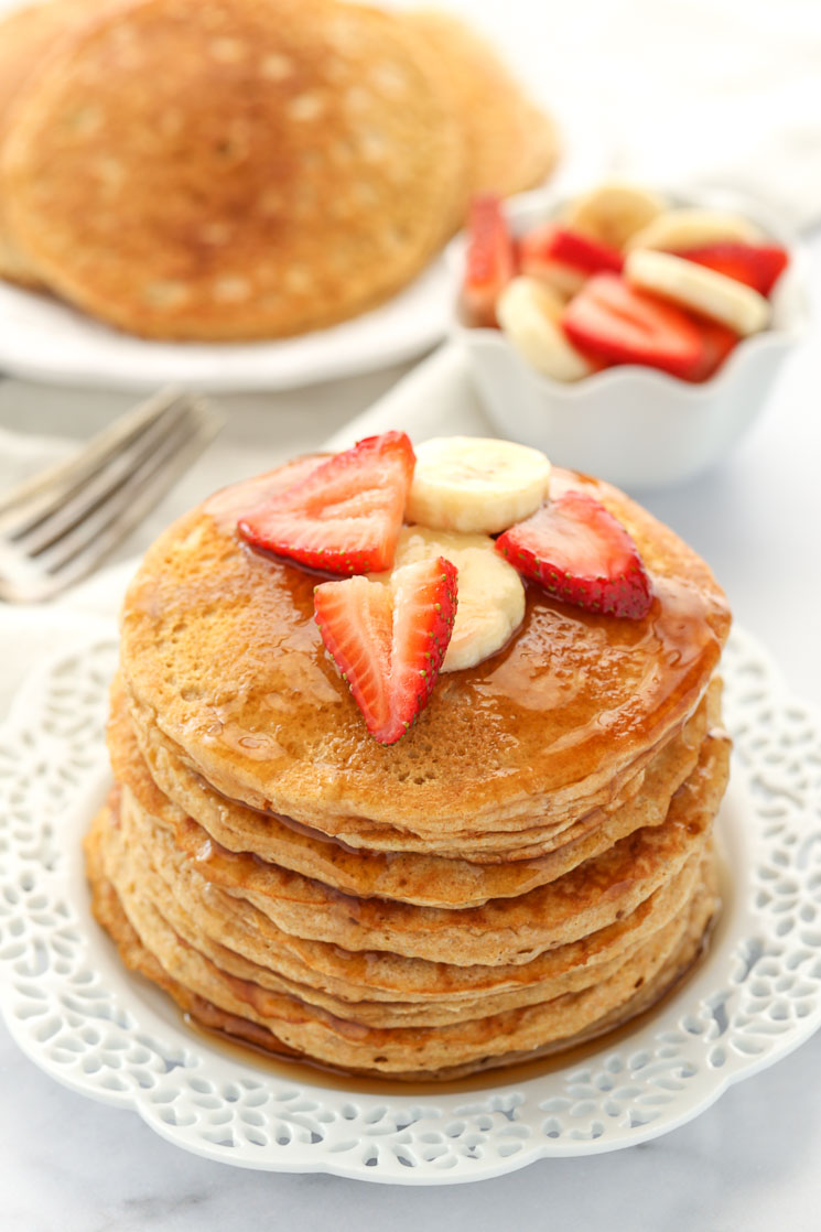 A stack of whole wheat pancakes topped with strawberry slices, banana slices, and maple syrup.