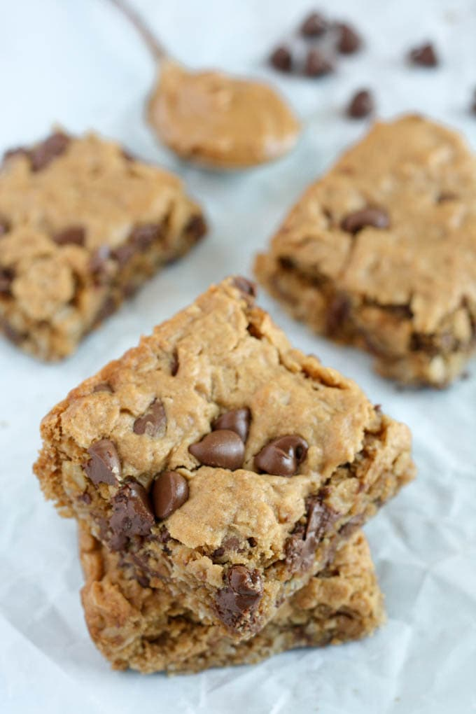 Four oatmeal breakfast bars next to a spoonful of peanut butter and a handful of chocolate chips.