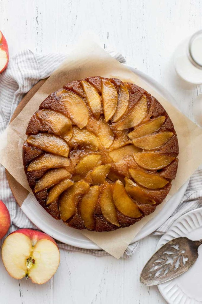 An overhead view of an apple upside-down cake with sliced apples and milk around it.
