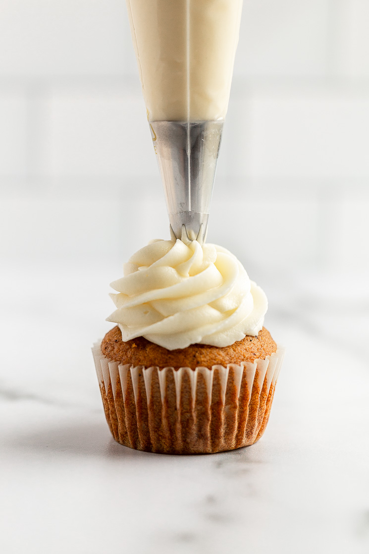 A single pumpkin cupcake being topped with cream cheese frosting using a piping bag.