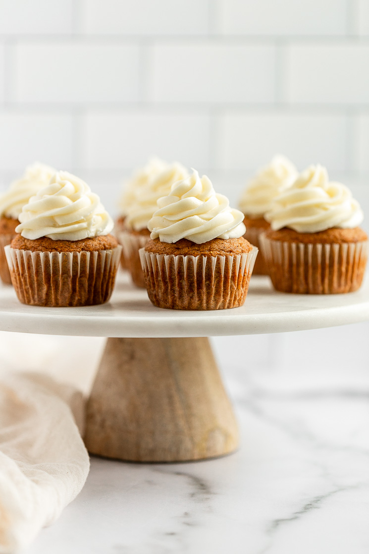 A group of pumpkin cupcakes topped with cream cheese frosting setting on top of a marble cake stand.