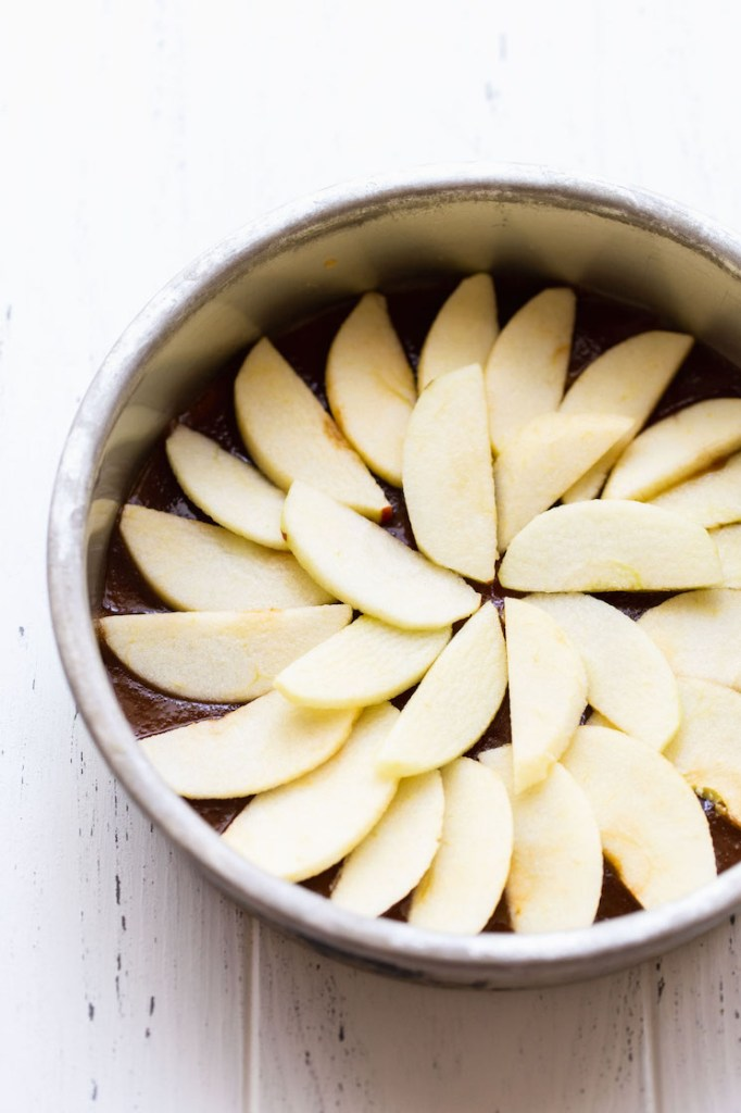 A round metal baking dish holding the caramel topping and apples arranged into a circle.