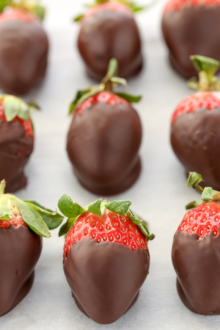 Chocolate covered strawberries lined up on a piece of parchment paper.