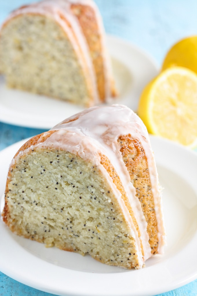 A slice of lemon poppy seed cake with glaze on a white plate. Lemon halves and another slice of cake rest in the background.