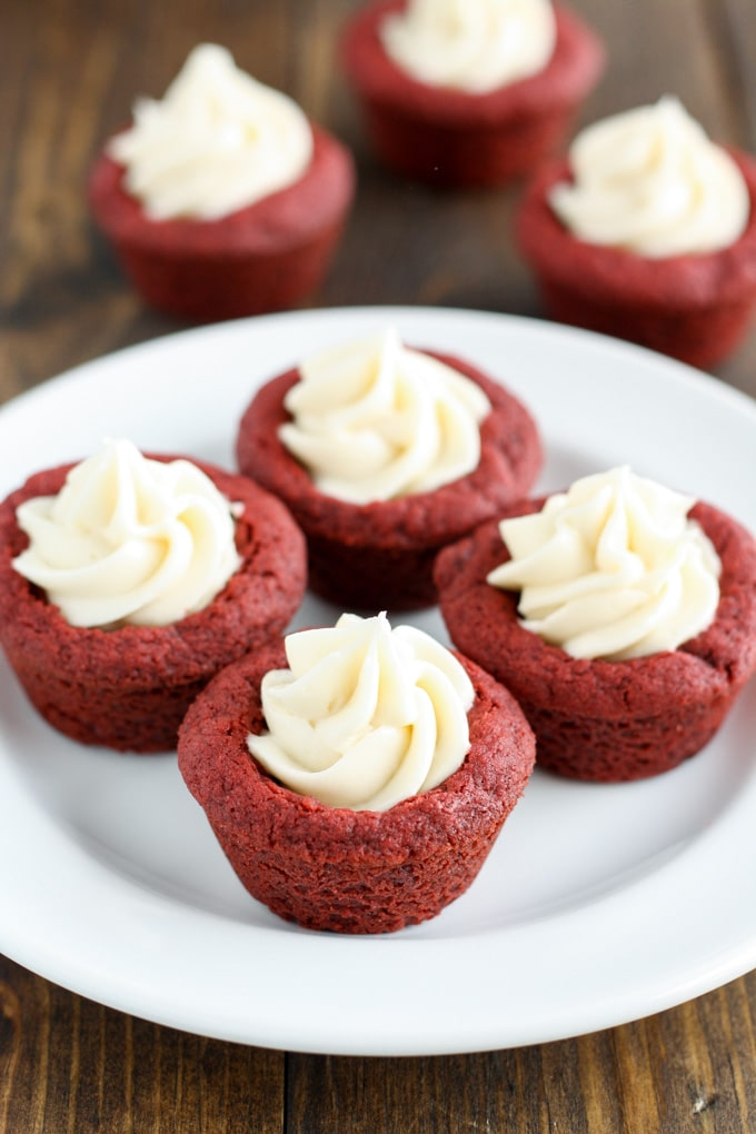 Four red velvet deep dish cookies with cream cheese frosting on a white plate.