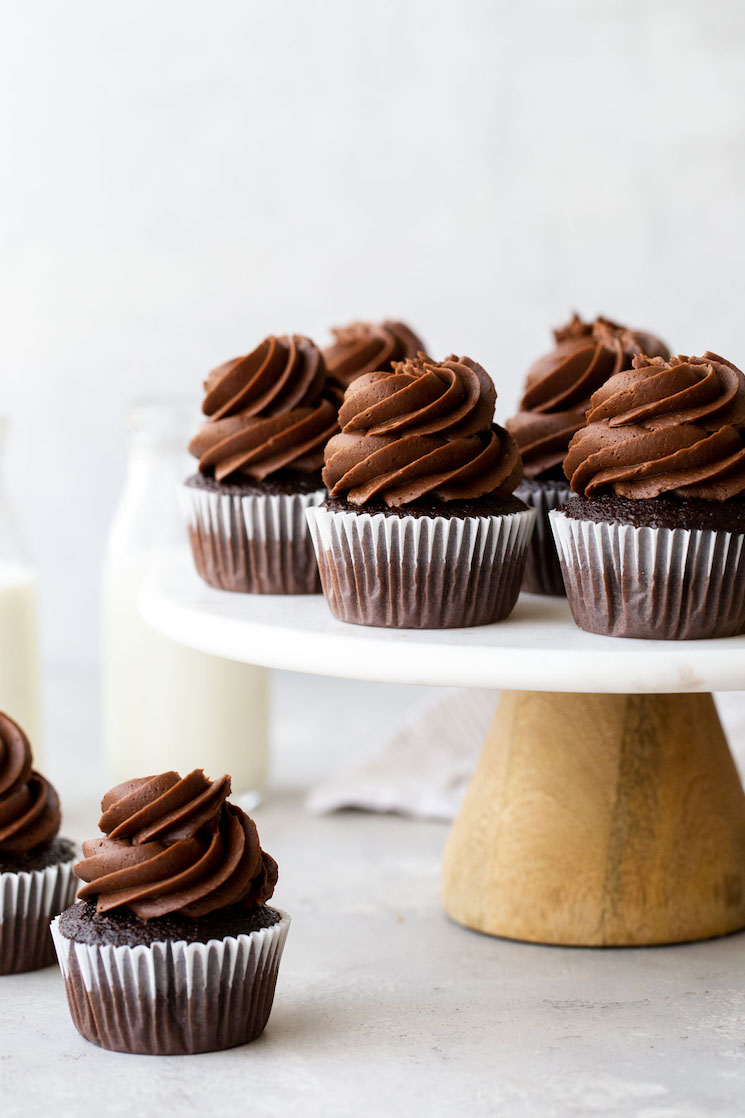 A marble cake stand holding chocolate cupcakes topped with chocolate frosting with jugs of milk in the background.