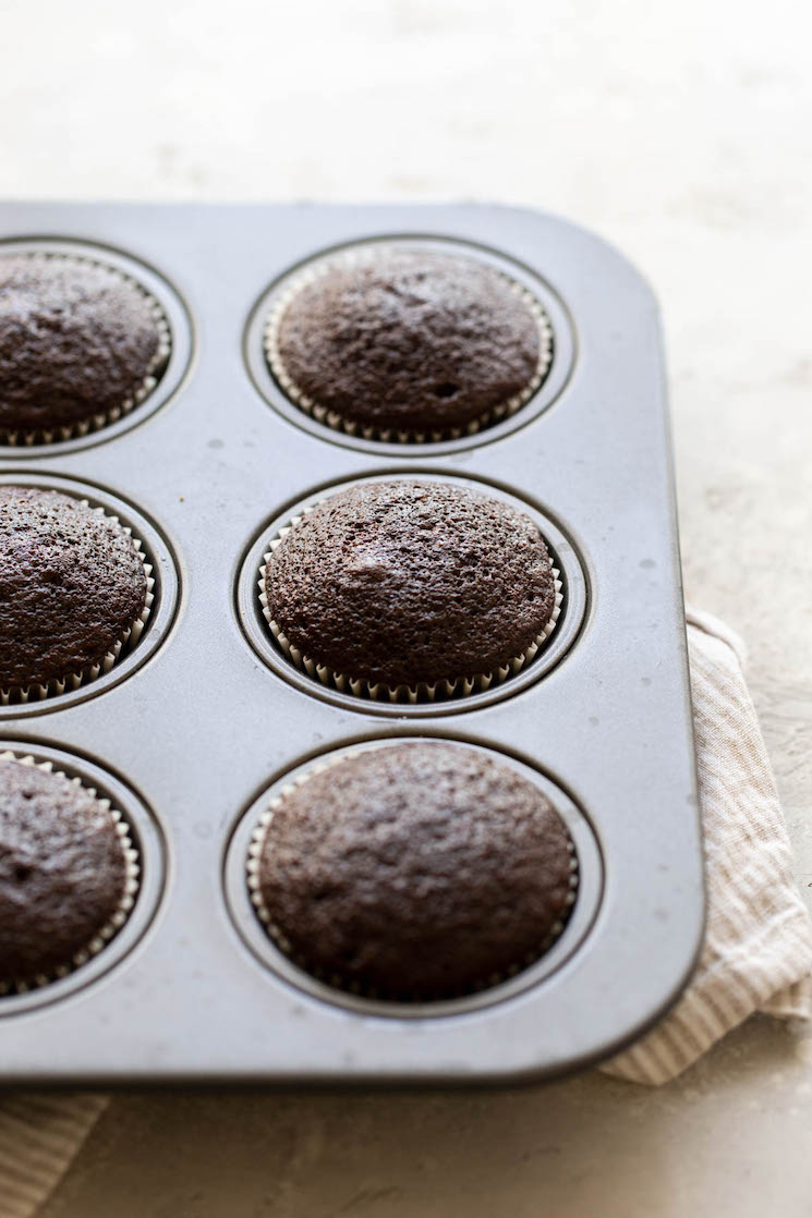 A muffin pan holding baked cupcakes on a rustic surface.