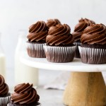 Several chocolate cupcakes on top of a marble cake stand.