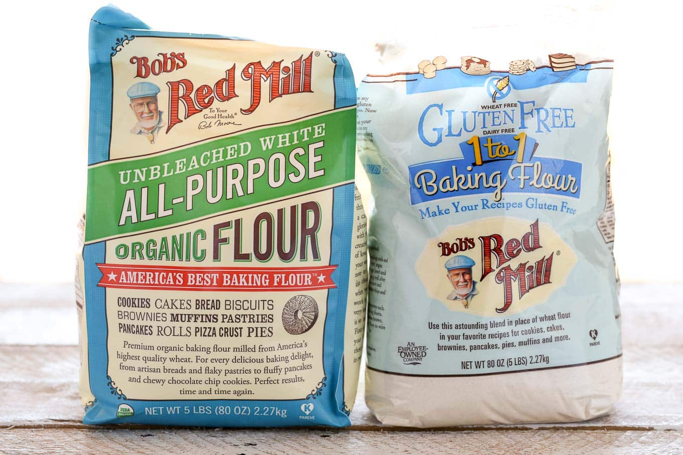 A bag of Bob's Red Mill all-purpose flour next to a bag of gluten-free 1:1 flour.