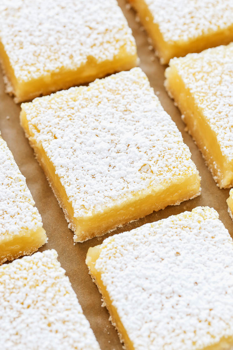 Sliced lemon bars on a piece of brown parchment paper.