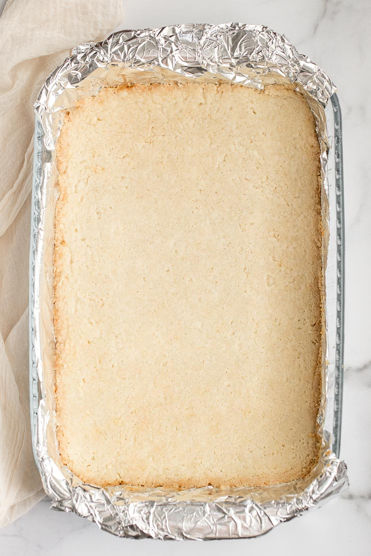 The baked shortbread crust in a pan lined with aluminum foil.
