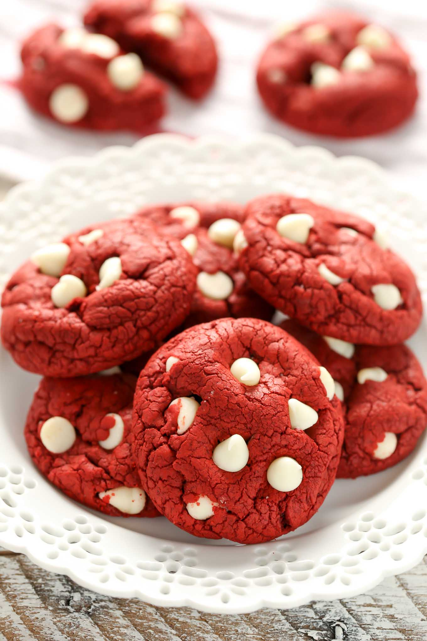 A white plate piled high with red velvet cookies. Two extra cookies rest in the background.