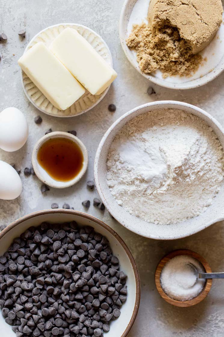 The ingredients needed to make chocolate chip cookies in bowls on top of a rustic gray surface.