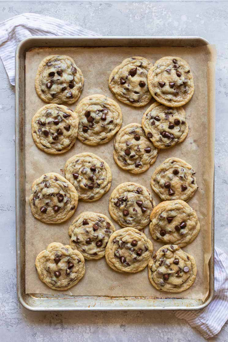 A baking sheet lined with brown parchment paper holding baked chocolate chip cookies.