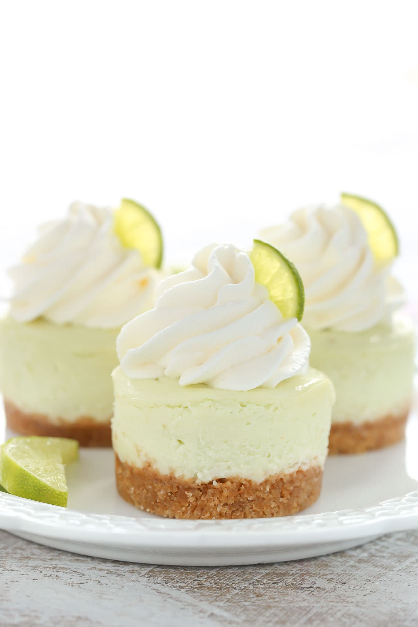 These Mini Key Lime Cheesecakes feature an easy homemade graham cracker crust topped with a smooth and creamy key lime cheesecake filling. The perfect dessert for any time of year!