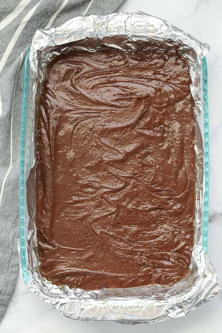 A clear pan lined with aluminum foiled and brownie batter spread evenly in the pan.