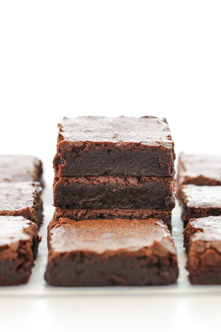A stack of sliced brownies on top of a piece of parchment paper with other brownies around it.
