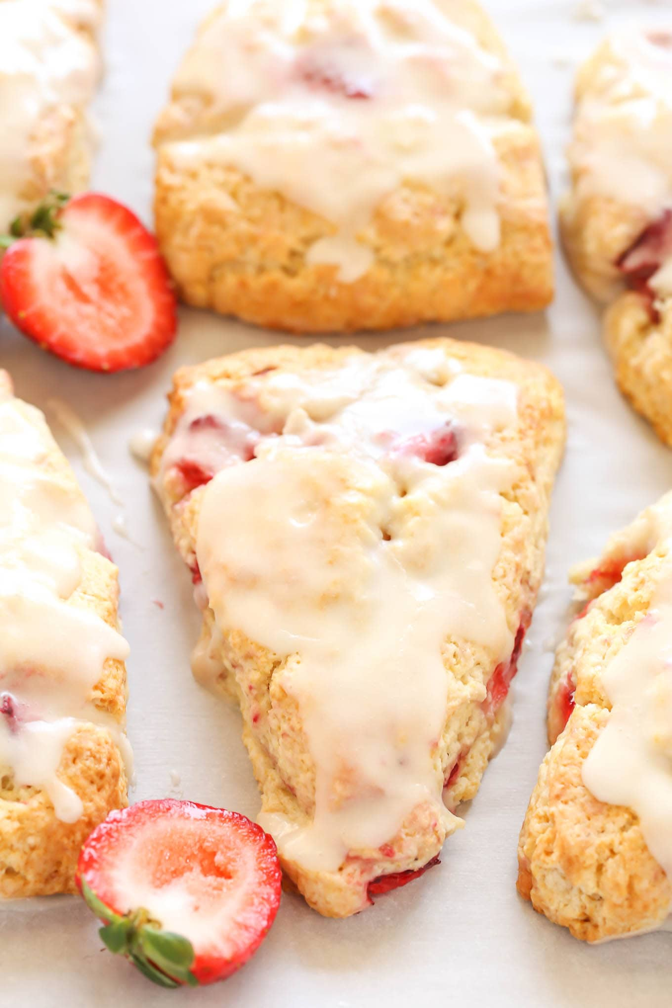 Six strawberry scones topped with glaze. Two strawberry halves rest between the scones.