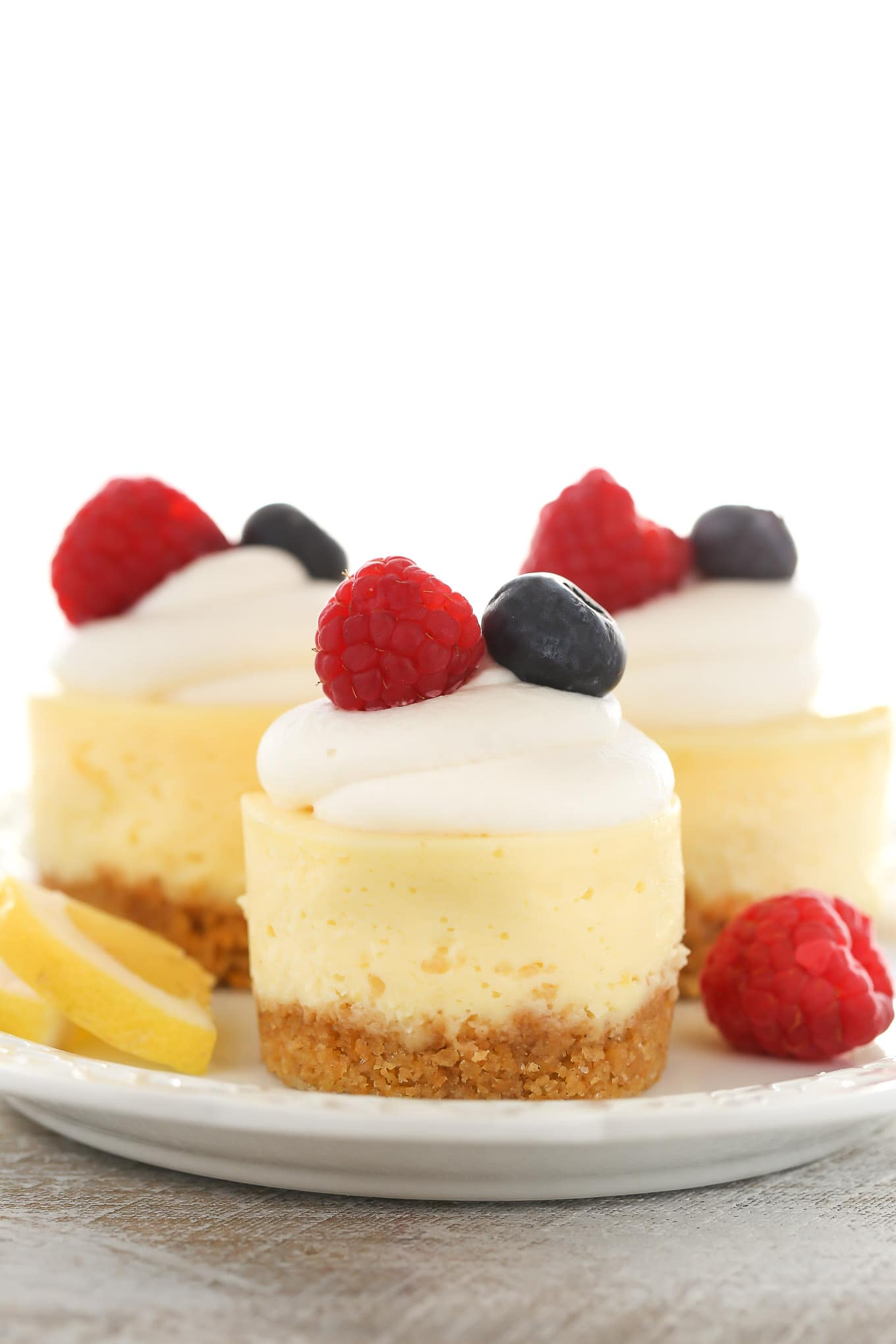 A side view of three lemon cheesecake bites on a white plate. Each is topped with whipped cream and fresh berries.