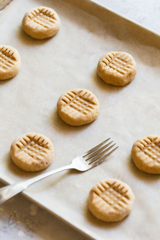 A baking sheet holding peanut butter balls pressed down with a fork to get the criss cross pattern.
