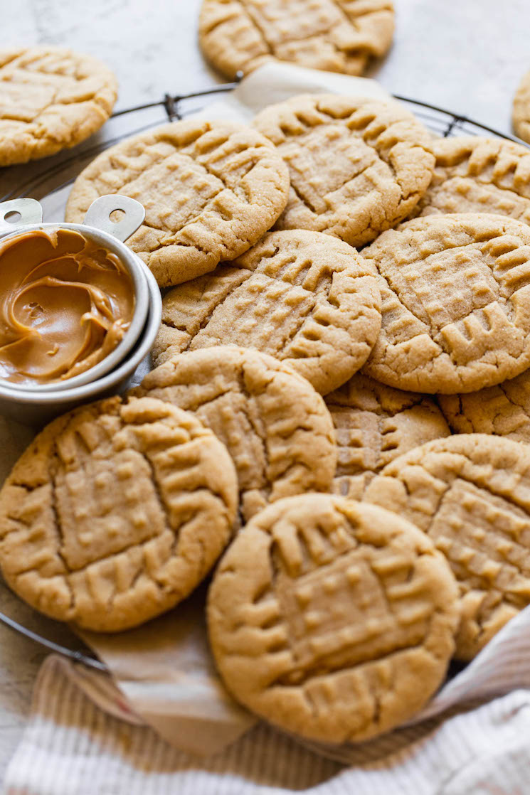A round cooling rack holding peanut butter cookies piled on each other with a small metal cup of peanut butter off to the side.