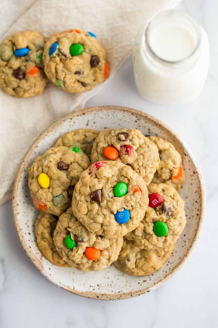 Monster cookies on a plate with more cookies and milk on the side.