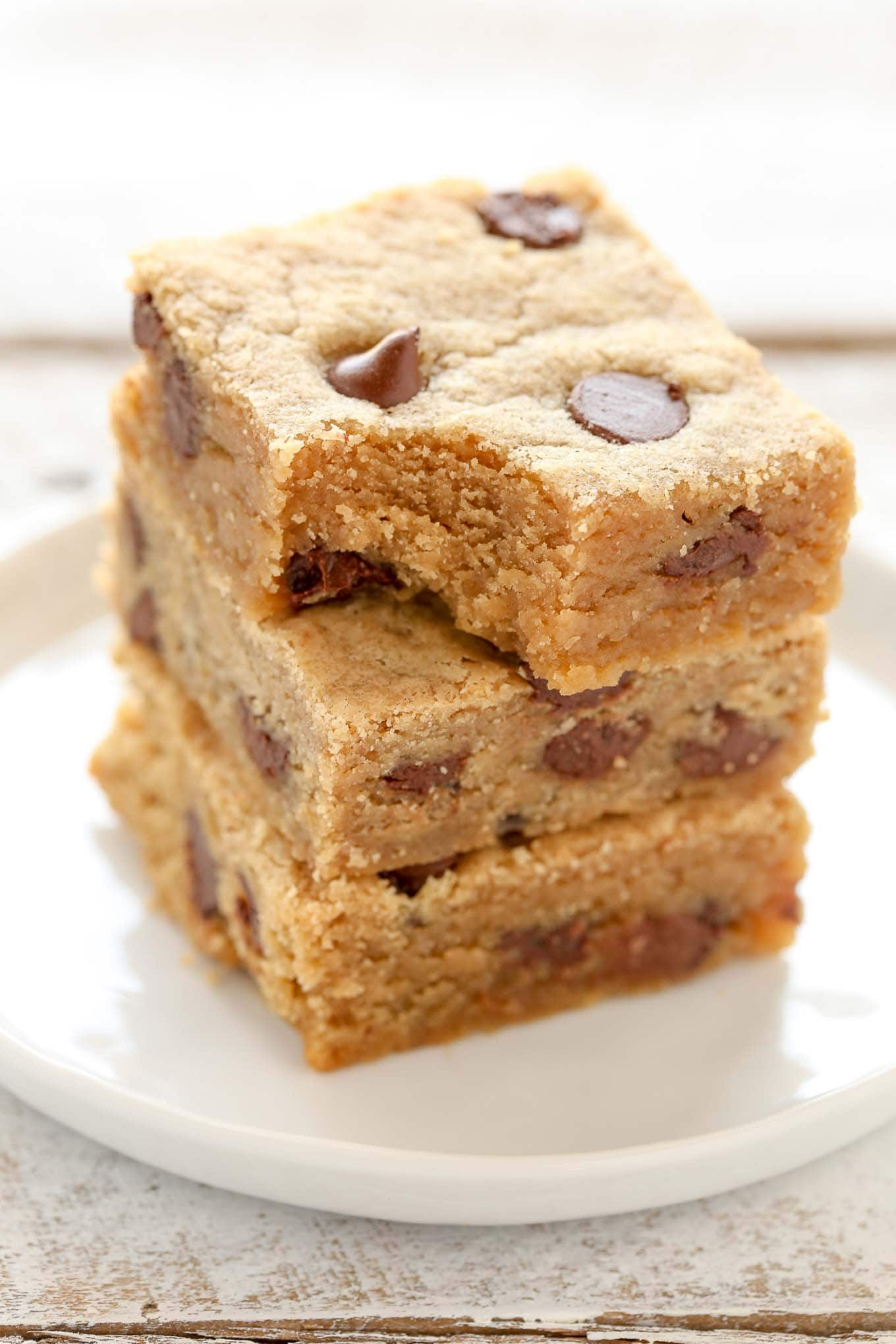 A stack of three peanut butter chocolate chip bars on a white plate. The top bar has a bite missing.