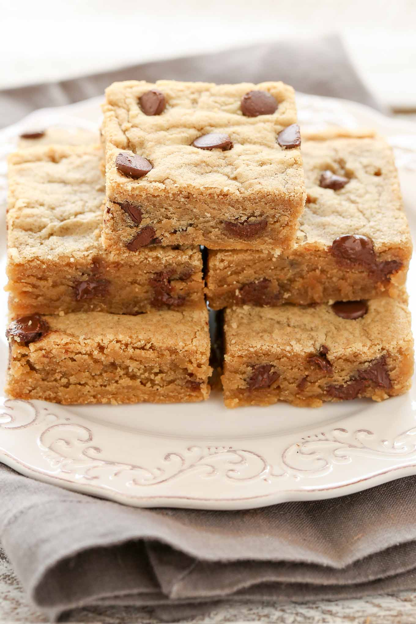 Five peanut butter chocolate chip bars stacked on a white plate.