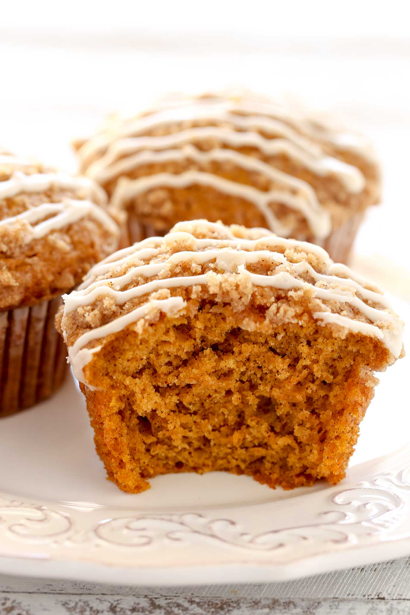 Close up view of pumpkin muffins on a white plate. The front muffin has a bite missing.