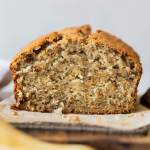 A straight on shot of a loaf of banana bread with the end cut off to show the breads texture.