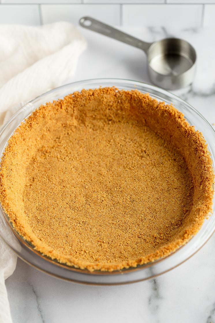 A baked graham cracker crust in a pie plate with a measuring cup behind it.