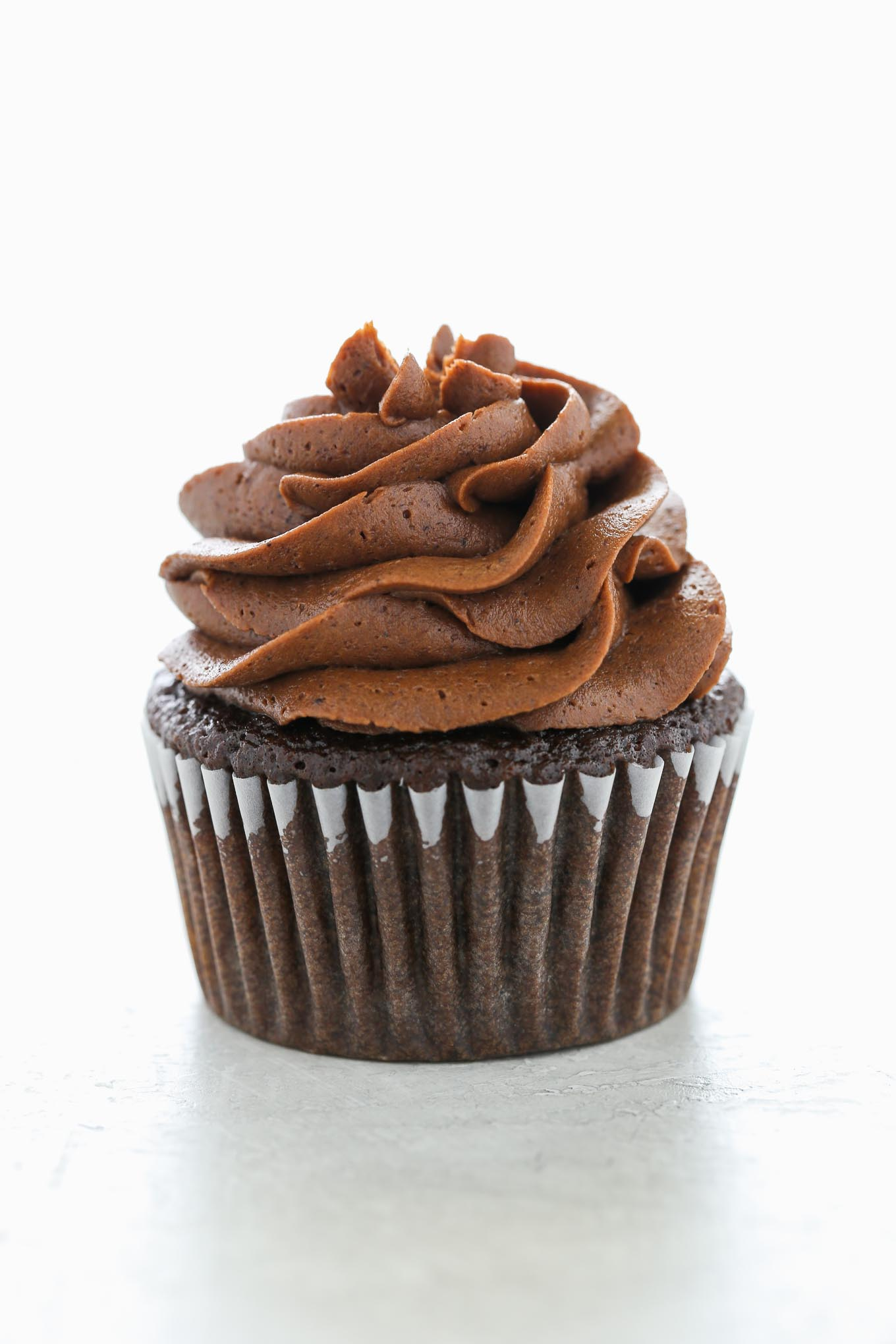 A single chocolate cupcake topped with a swirl of chocolate buttercream frosting.