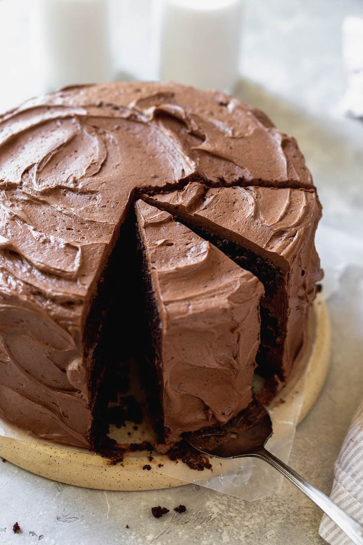 A chocolate cake sitting on a round board with a couple of pieces sliced.