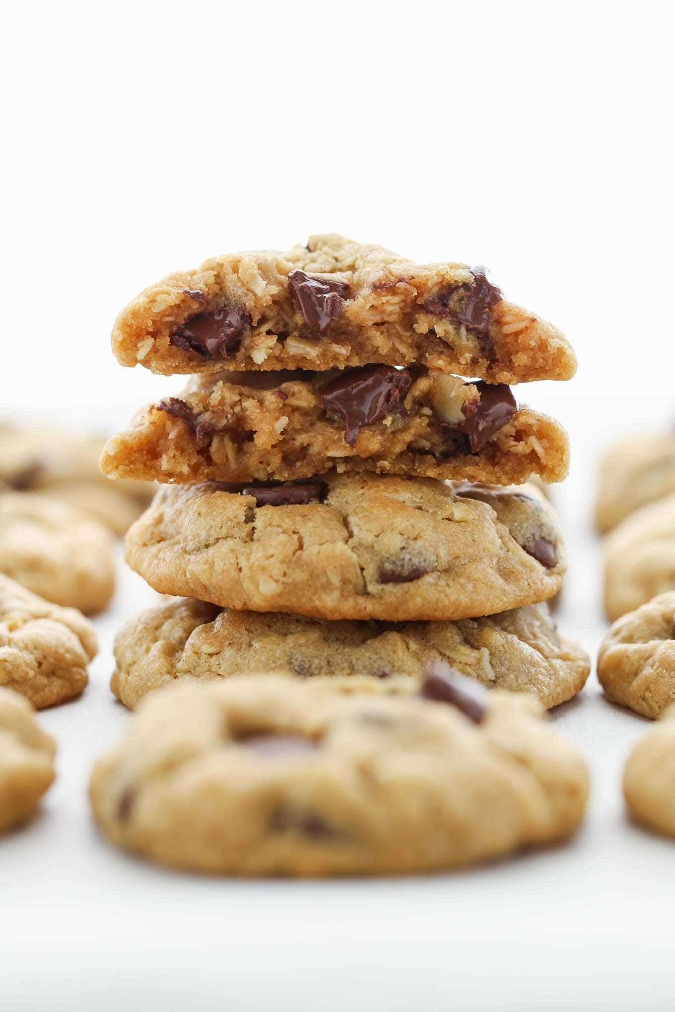 A stack of peanut butter oatmeal chocolate chip cookies with more cookies surrounding them.