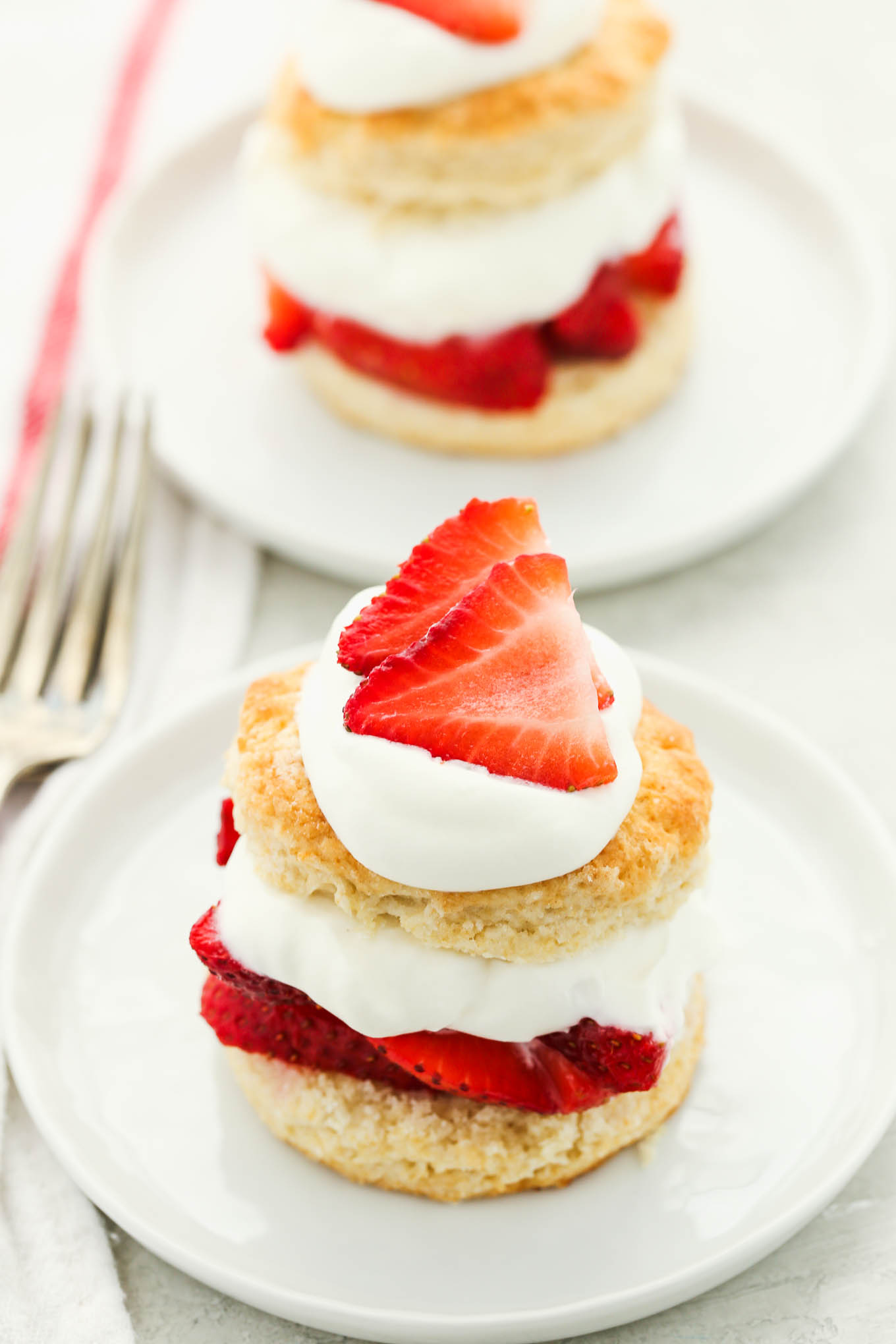 Two prepared strawberry shortcakes topped with extra whipped cream and sliced strawberries on white plates.