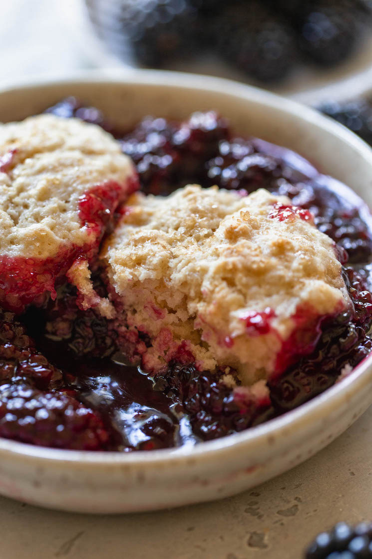 An antique bowl holding blackberry cobbler with a bite taken out of the biscuit topping to show the texture.