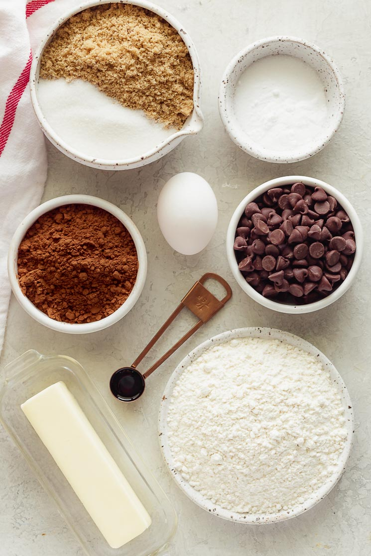The ingredients needed for double chocolate chip cookies on a gray surface.