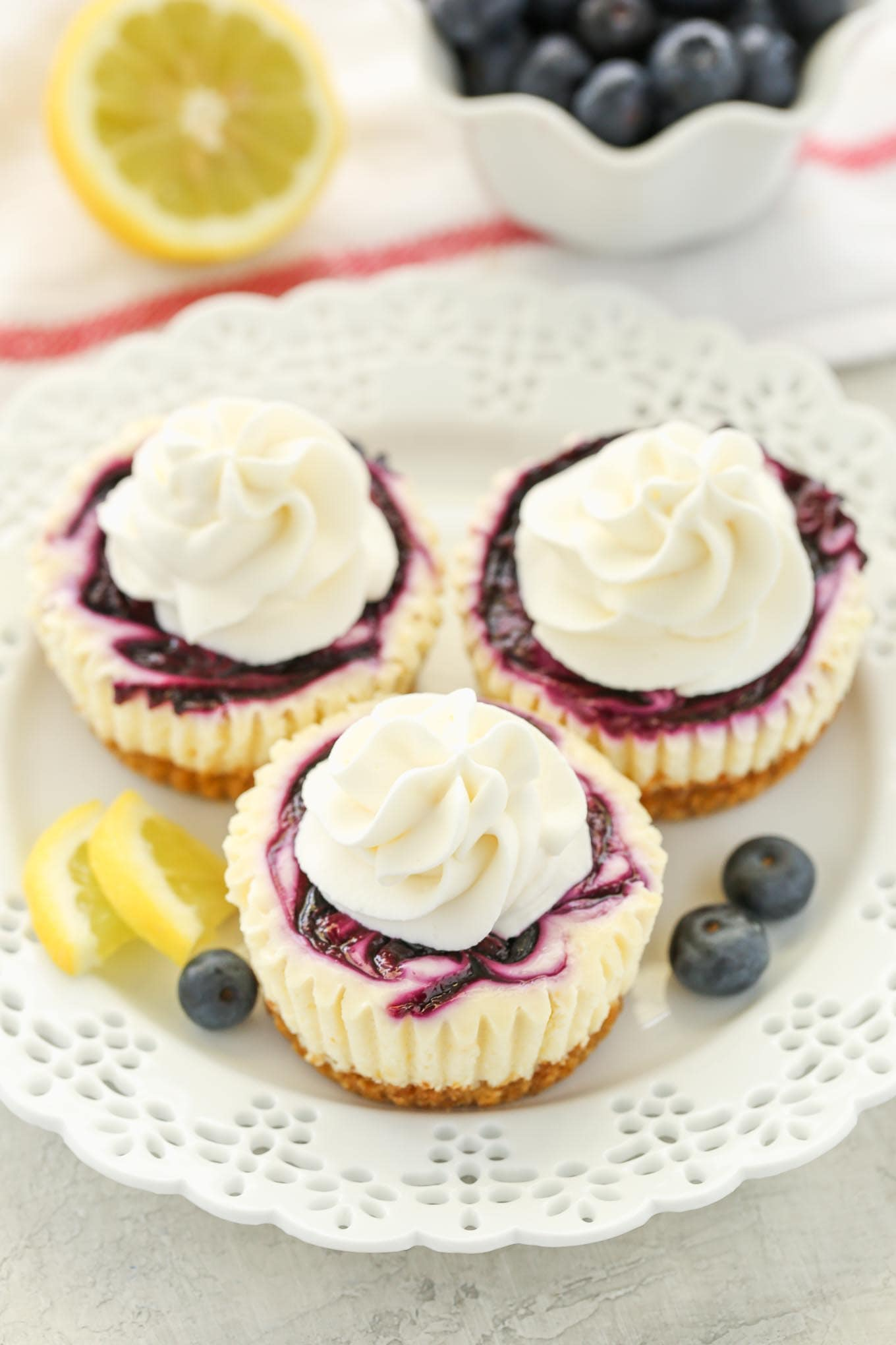 These Mini Lemon Blueberry Cheesecakes feature an easy homemade graham cracker crust, smooth and creamy lemon cheesecake filling, and a simple blueberry swirl!