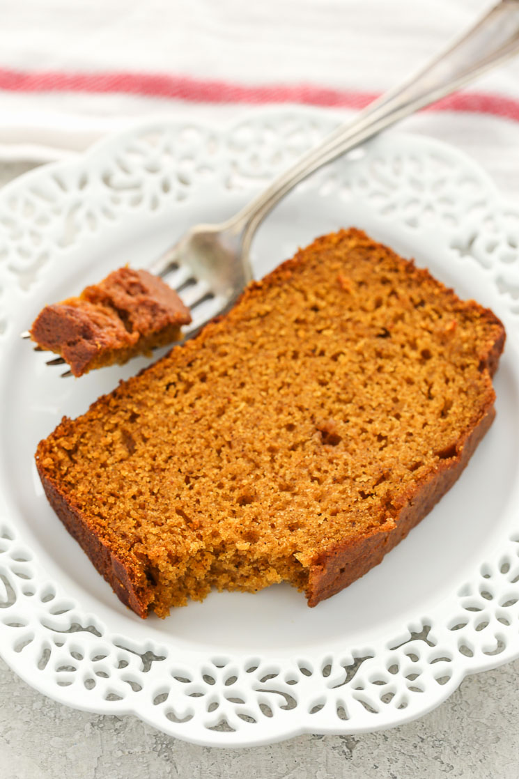 A slice of pumpkin bread on a white decorative plate.